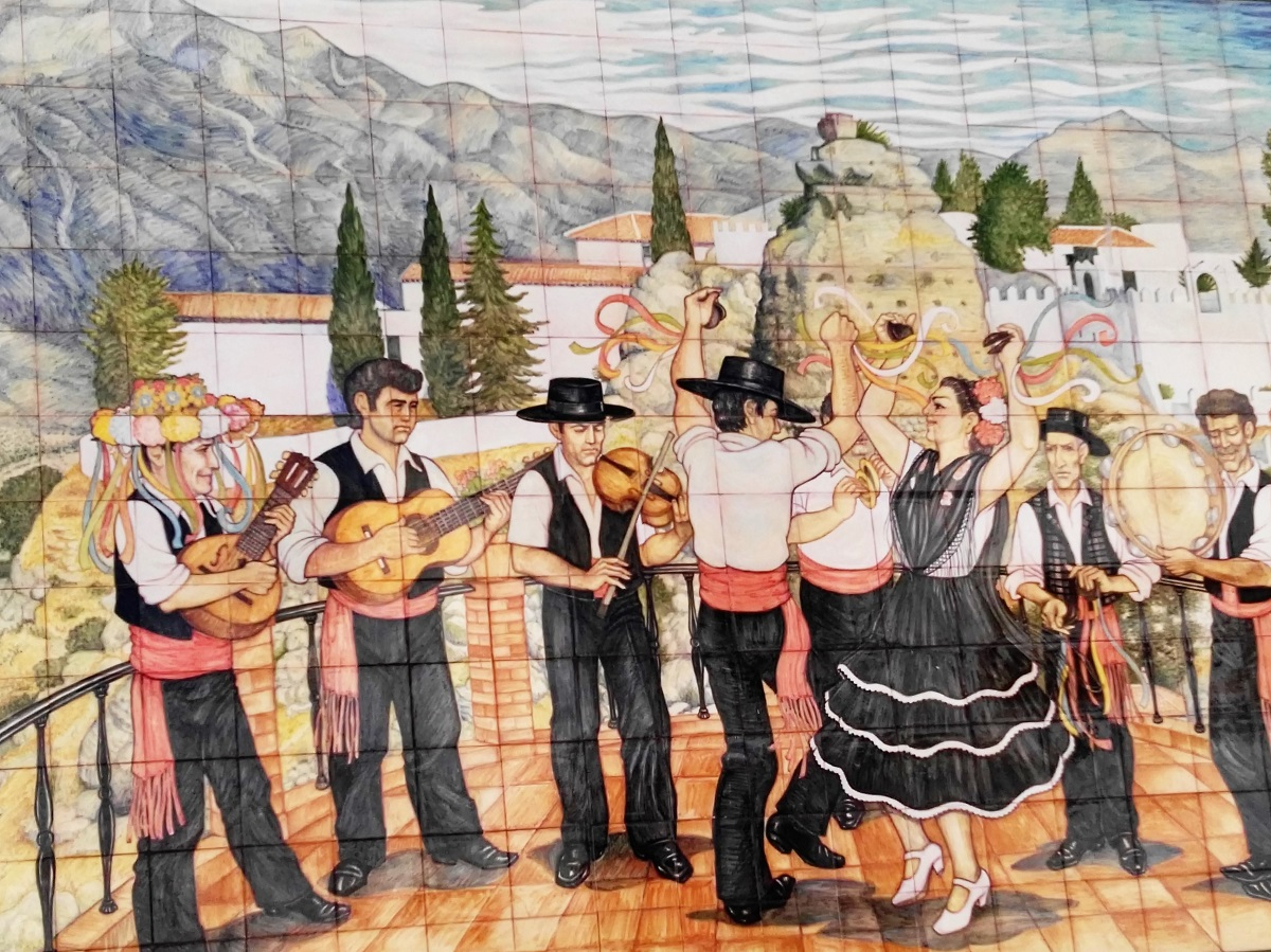 A-tiled-wall-in-Comares-tells-a-flamenco-story-note-the-town-and-ruined-castle-in-the-back-with-the-Sierras-