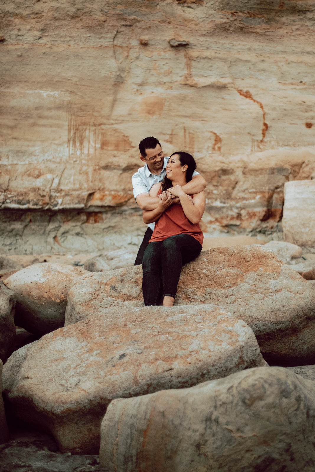 A couple sitting on a rock on the beach hugging