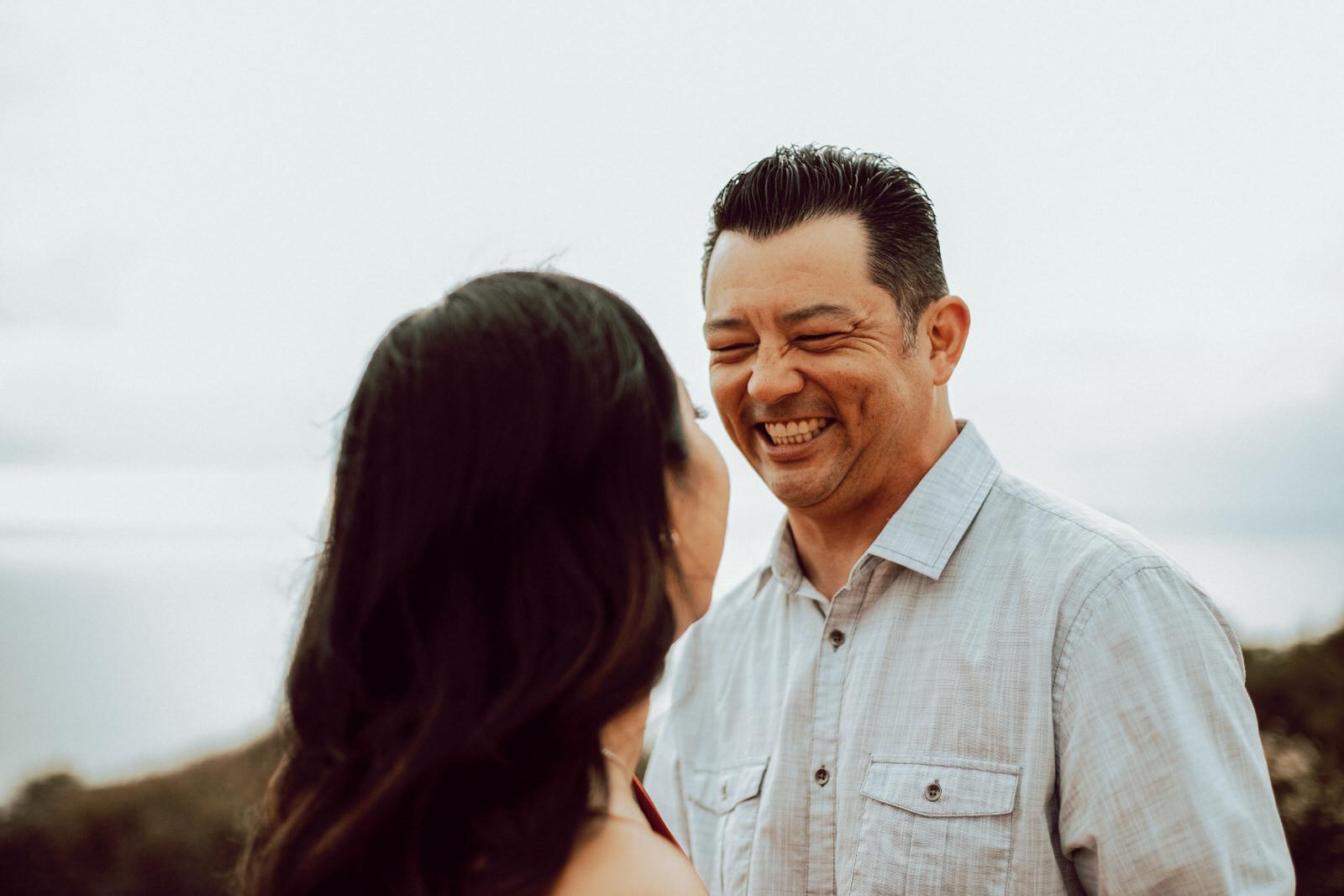 A tall man smiling at his girlfriend