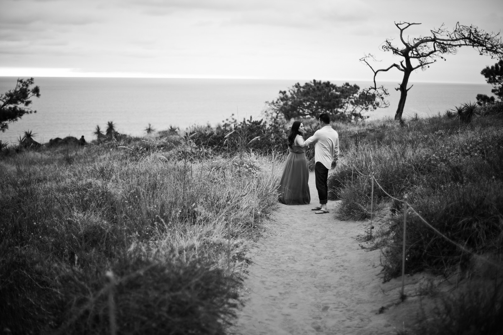 A black and white image of a man and woman walking down a beach trail