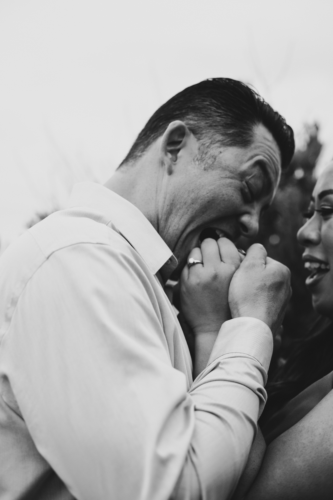 A man biting a woman's hand as she laughs