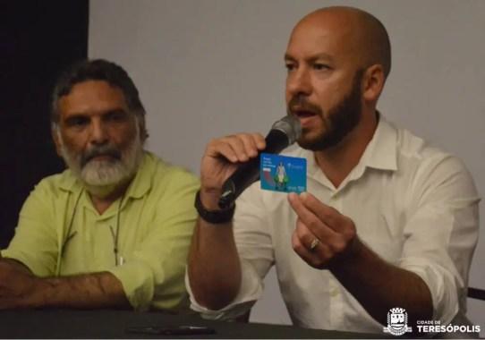 Prefeito Vinicius Claussen mostra o cartão do programa Ecoenel na solenidade de posse do COMDEMA