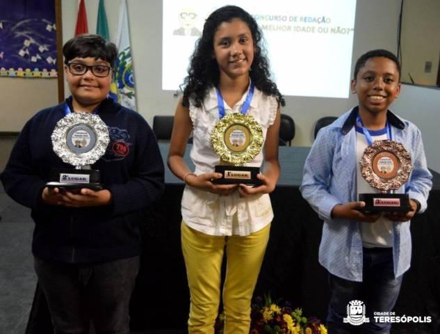 Jennifer Varela entre Gabriel Carino e Joshua Quintanilha, vencedores do concurso de redação