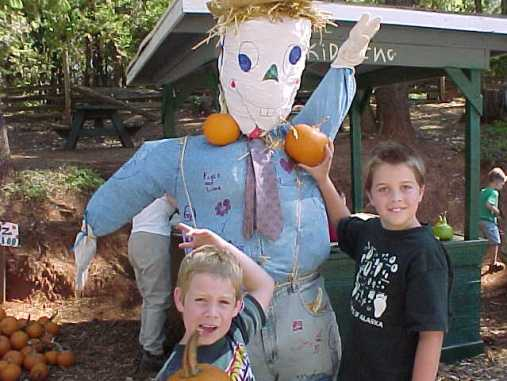 the author's children posing with a scarecrow and two small pumpkins