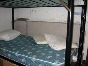 A bunkbed with naked mattress and three pillows