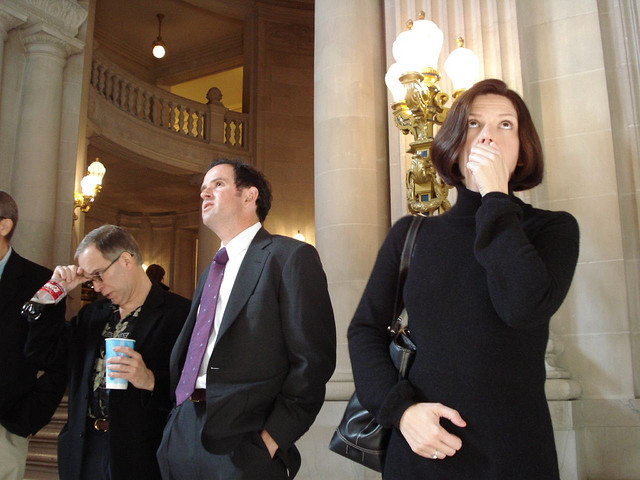 photo of a woman coughing in foreground with three disinterested men in the background
