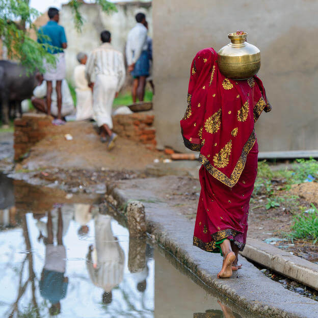 photo of a barefoot woman in a sari carrying a pot of water on her shoulder