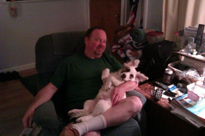 photo of the author's husband holding their corgle in his lap