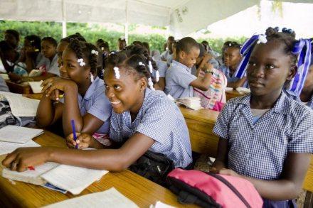 children, dressed in uniforms, sitting at desks in an outdoor school