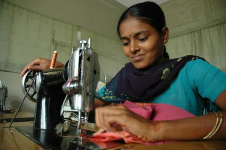 girl in sari, using an old-fashioned sewing machine