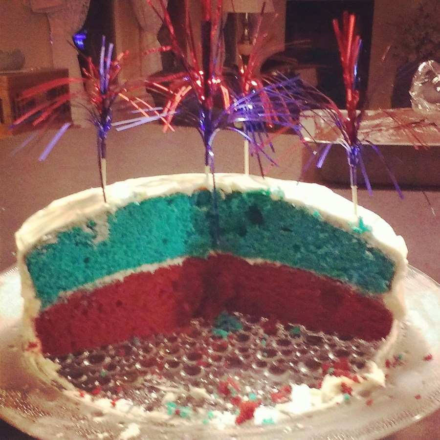 "photo of half a red, white and blue cake with red and blue ""sparkler"" decorations"