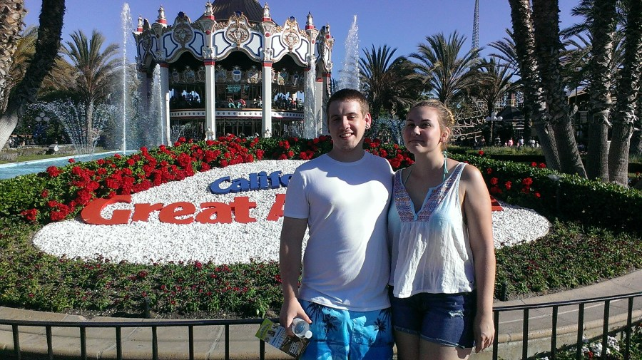 the author's son and his girlfriend posing in front of a carousel and the California's Great America sign