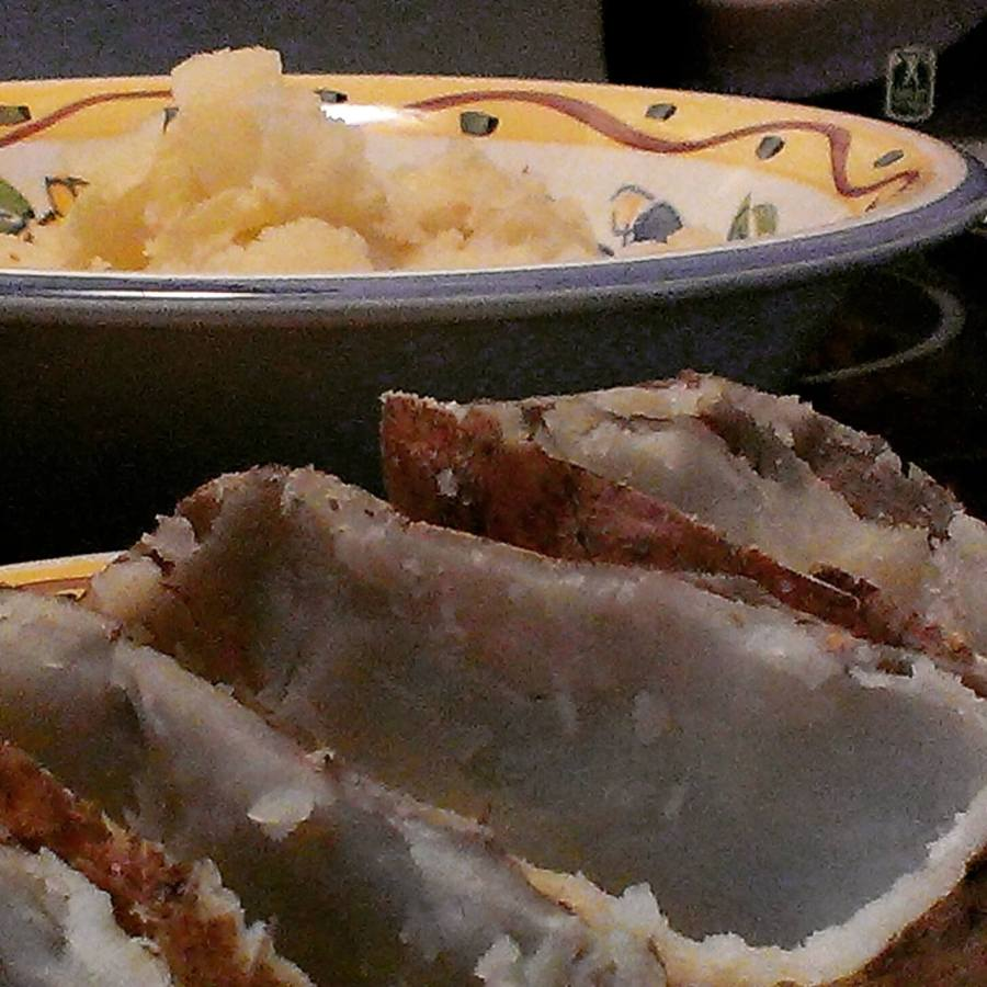 scooped-out potato skin with mashed potatoes in the background