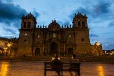 Dois homens sentados em um dos bancos da Plaza de Armas, em frente à Catedral da cidade