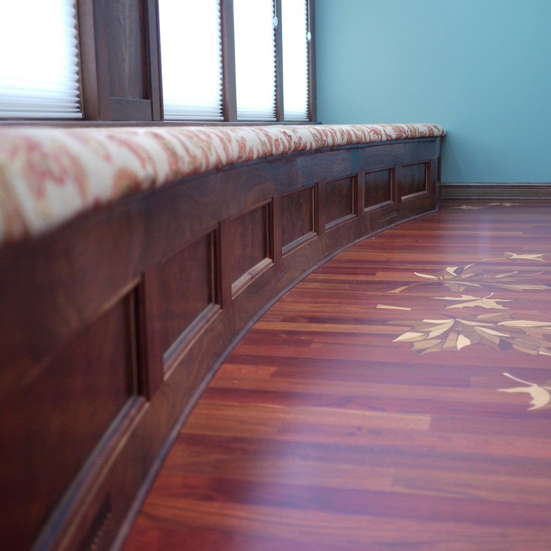 walnut built in curved bench with inlayed oak leaves