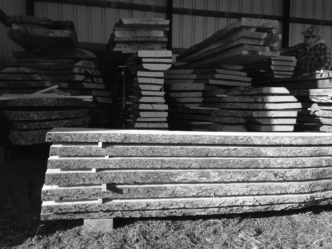 large stacks of milled lumber in barn with man in background