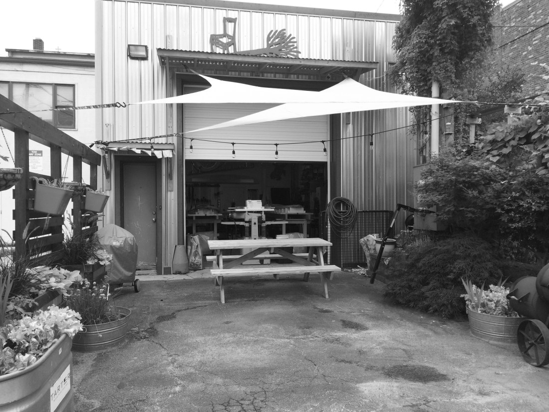 Urban Wood shop surrounded by urban garden with a picnic table