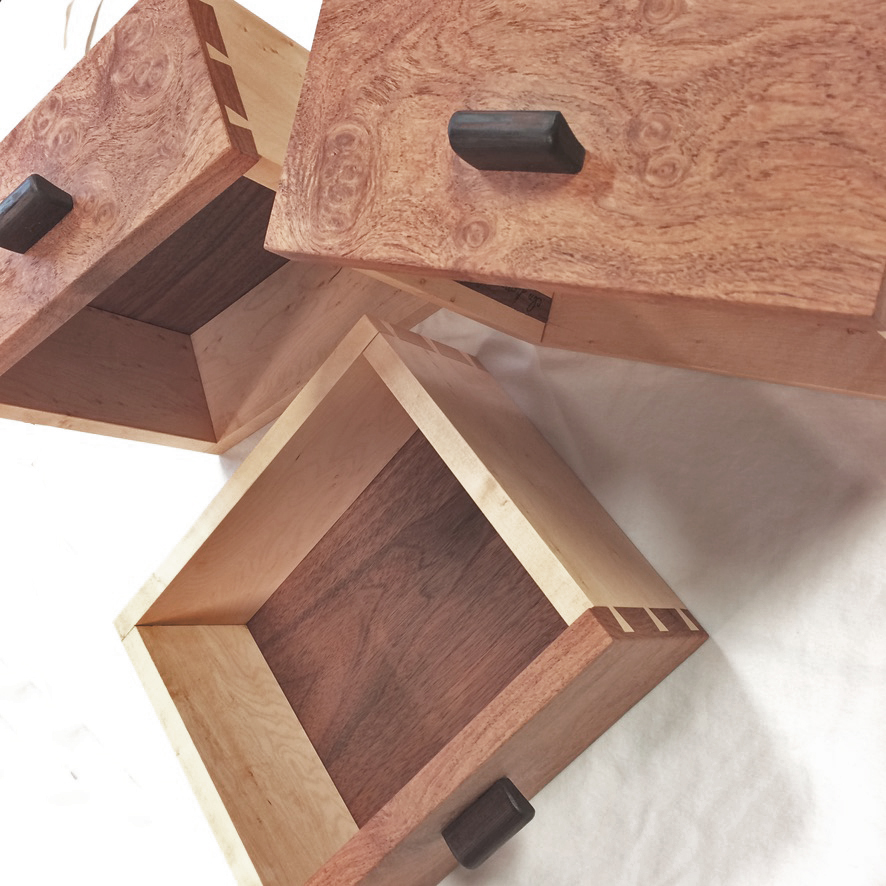 three solid wood drawers  with wenge pulls figured walnut face construction and maple side walls propped in multiple directions