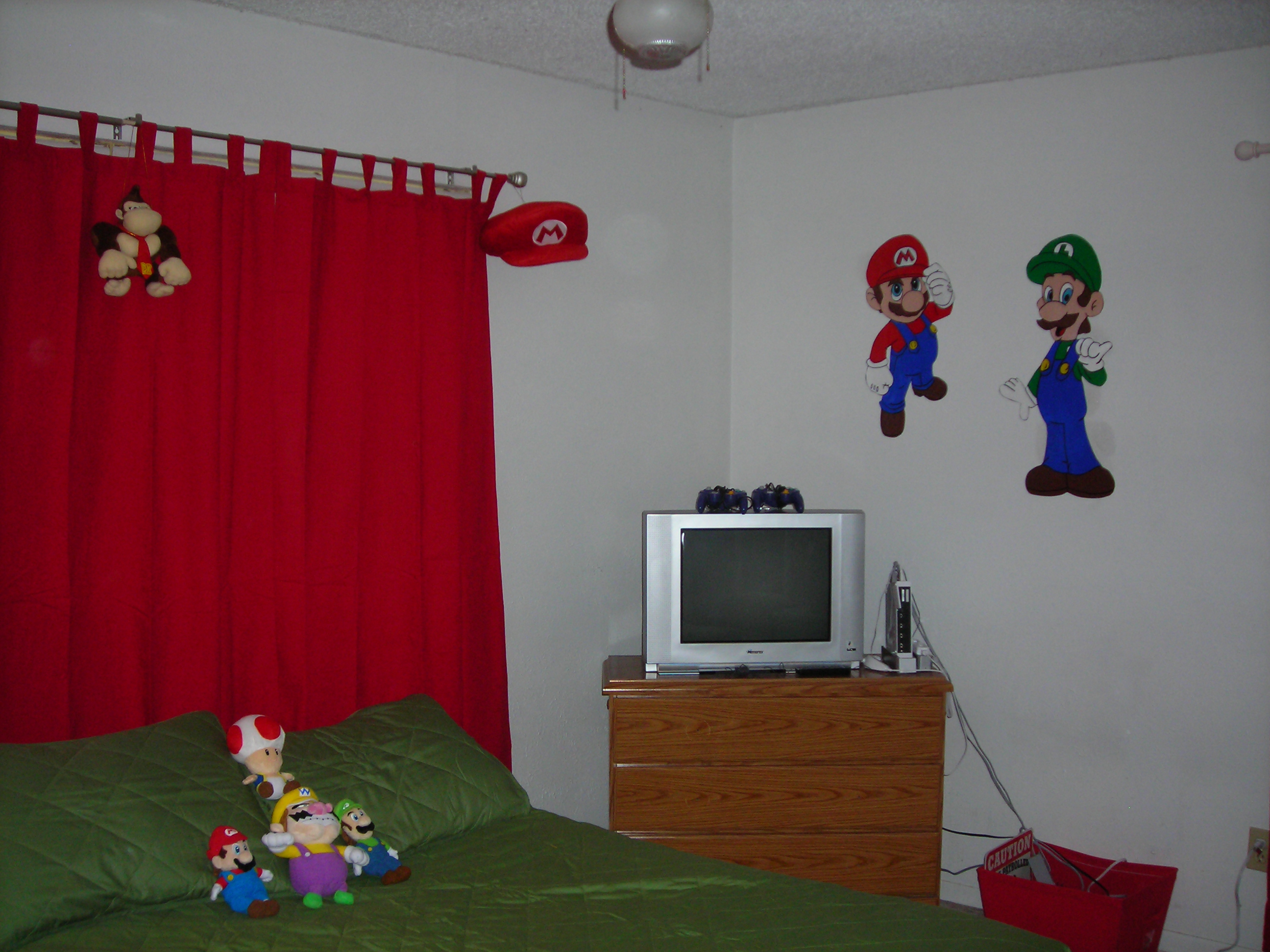 new red curtains (mario-inspired), new green bedspread (luigi-inspired), mario and luigi murals on wall, over his gaming area