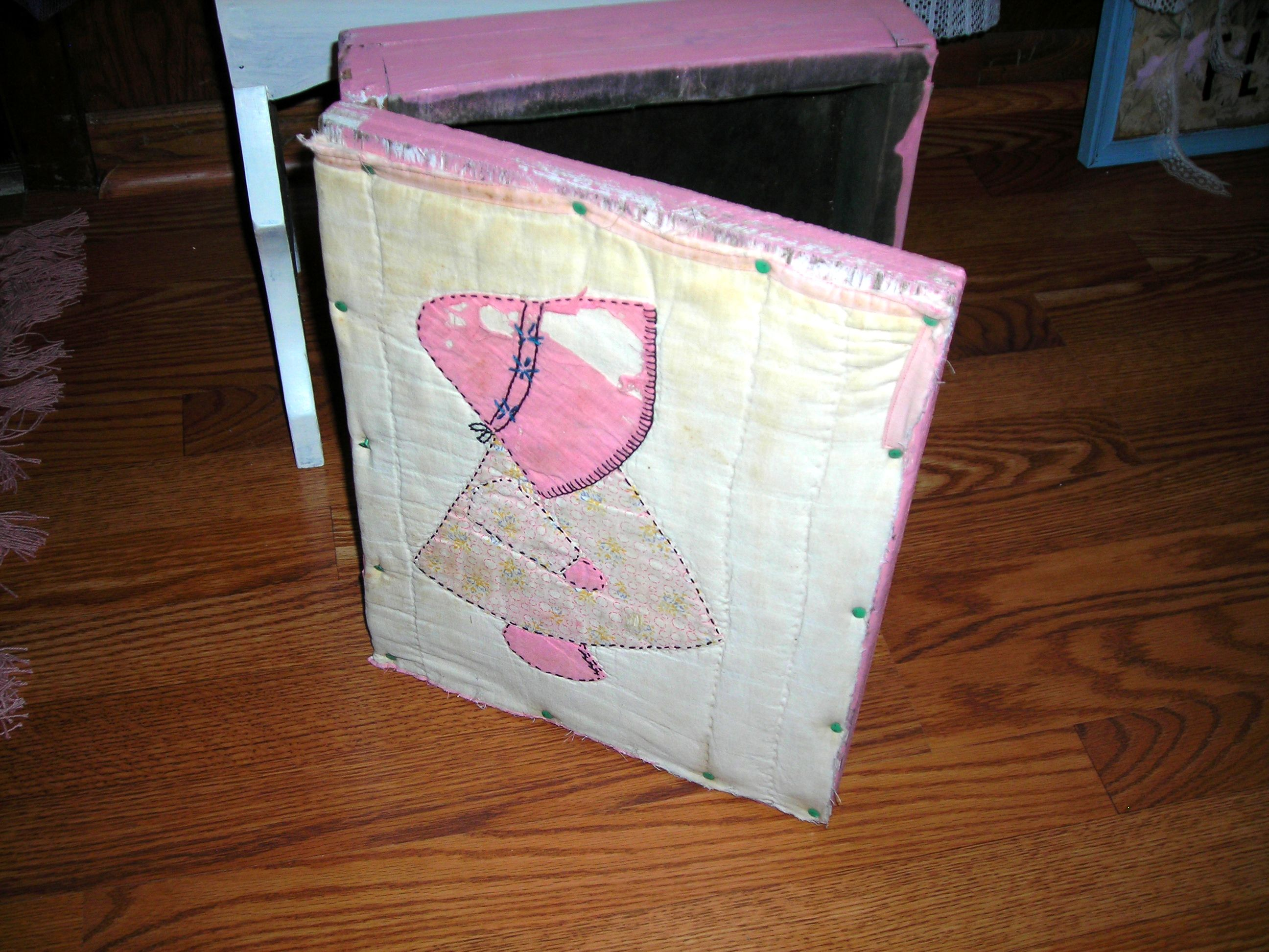it's an old box, painted pink with an old quilt piece on the cover.
