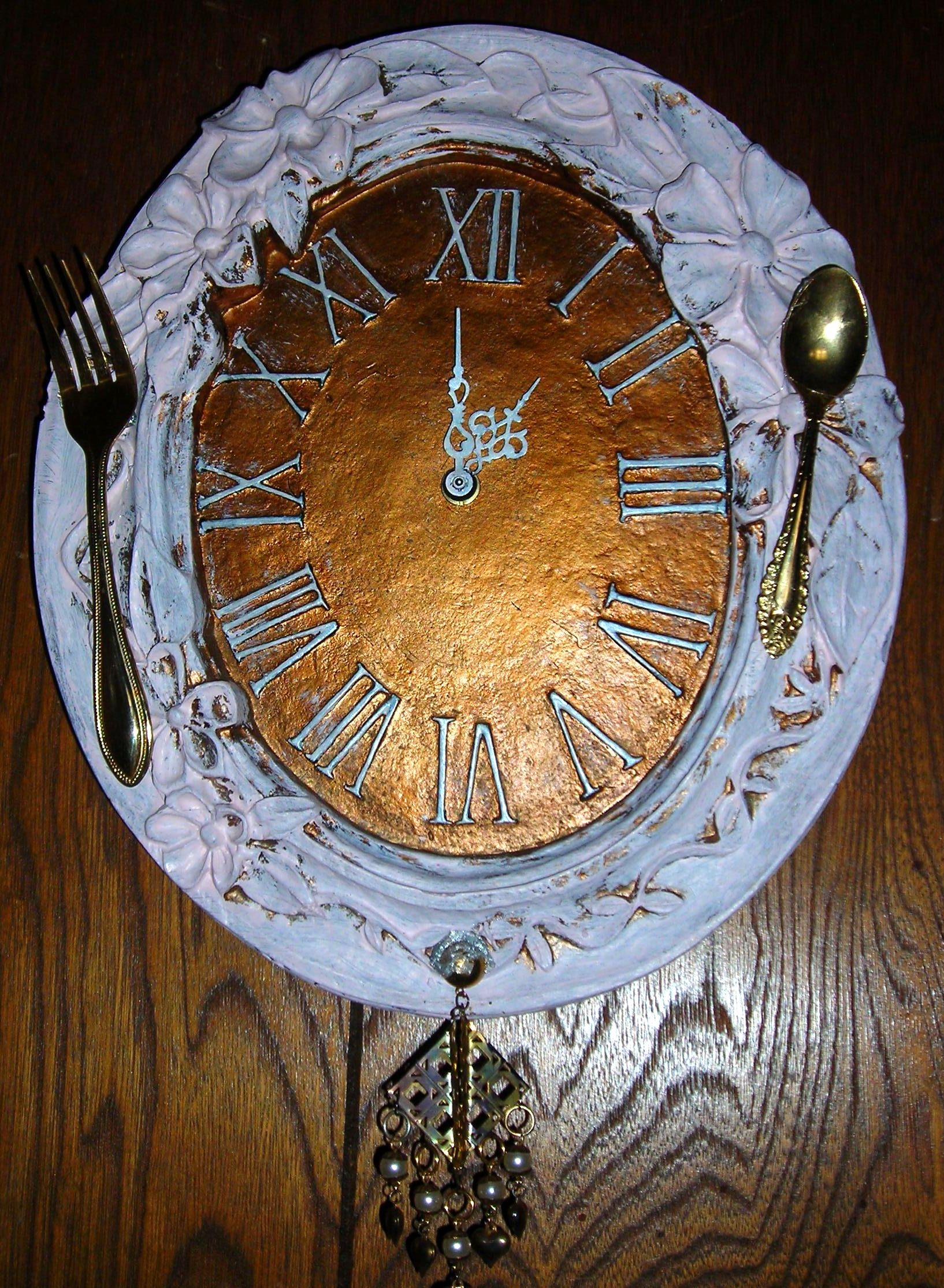 heavy old clock i found at the GW barn a long time ago. it worked, but didn't like that it was all goldtone. FINALLY painted the floral part, numbers and hands pink, glued an old fork and spoon on it (it's in the kitchen) and a castoff earring at the bottom.