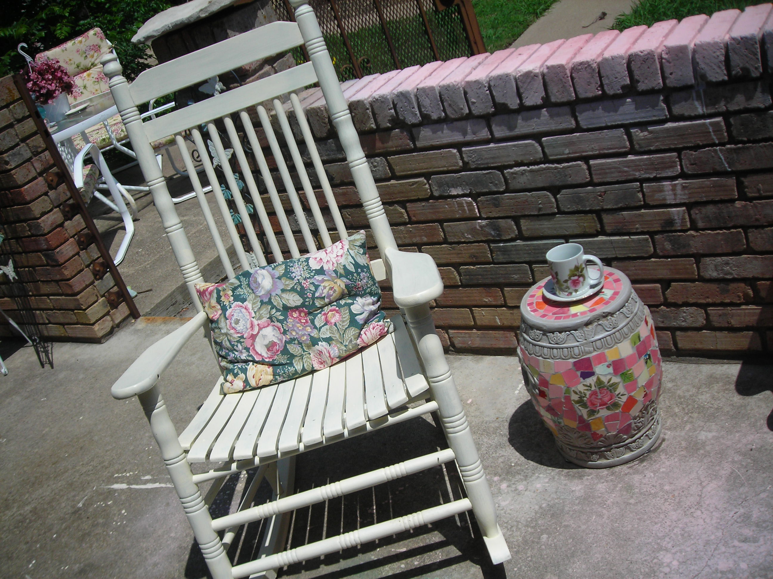 this is an old cracker barrel rocker that i found a few years back at an antique mall. painted it antique white and had been using it inside. i think it looks great on my patio. the mosaic piece next to it was marked way down at 'tuesday morning' because of a small chipped area. lucky me!
