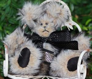 A dapper little beige and black tipped bear!