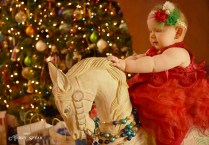 Baby in Christmas dress and on rocking horse 1000 183