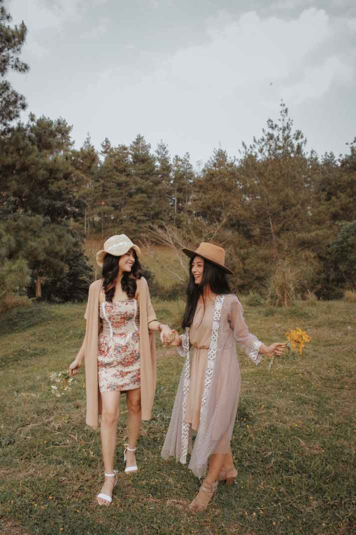 happy gorgeous young women holding hands and walking on grassy lawn in countryside