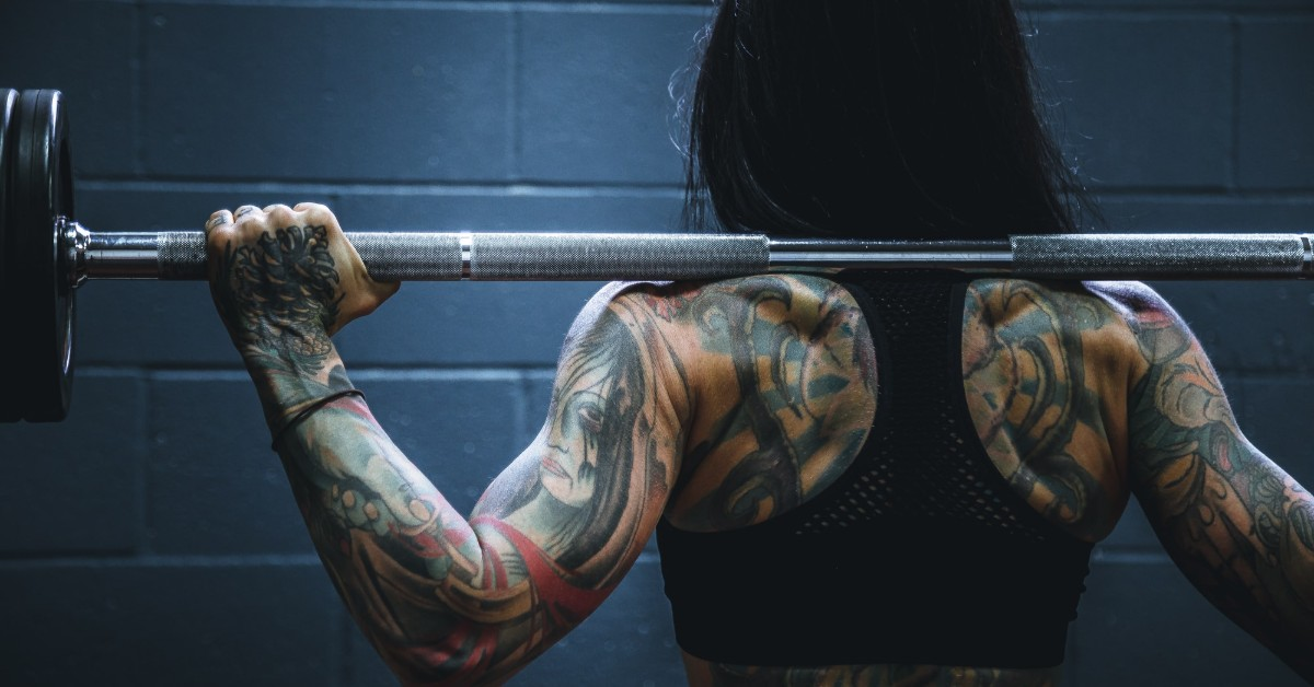 A muscular tattooed woman with weights resting on her shoulders