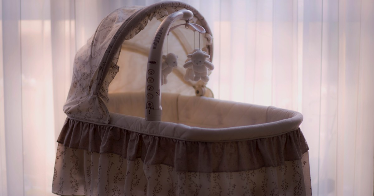 an empty baby cradle with a crib mobile
