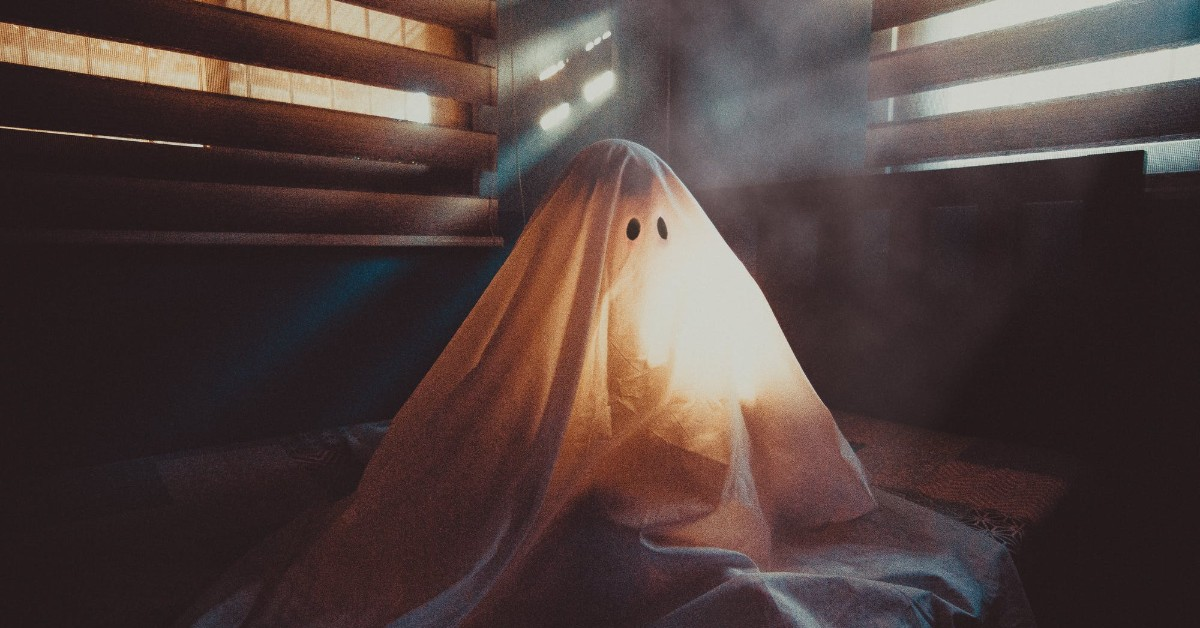 Ghost in a white sheet sitting in an eerie room