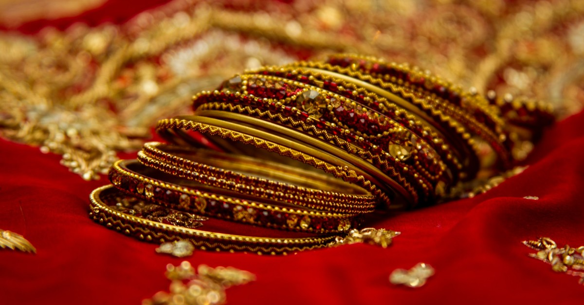 golden red bangles lying on a red wedding saree