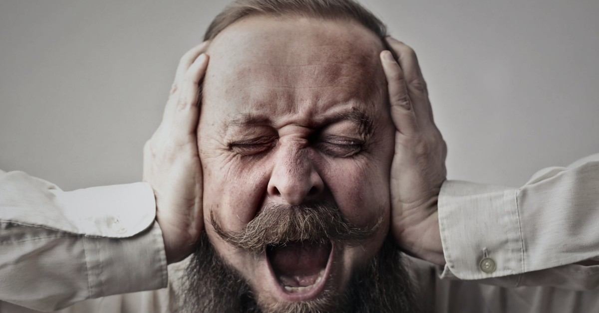 A white bearded man holding his head and screaming