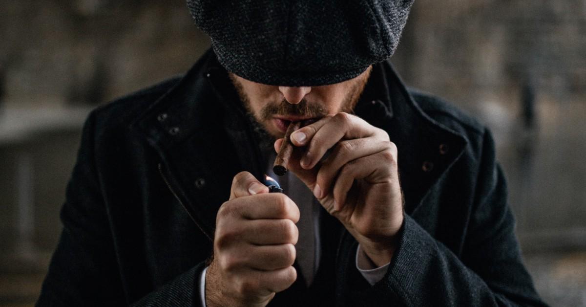 A man in a cap lighting a cigar