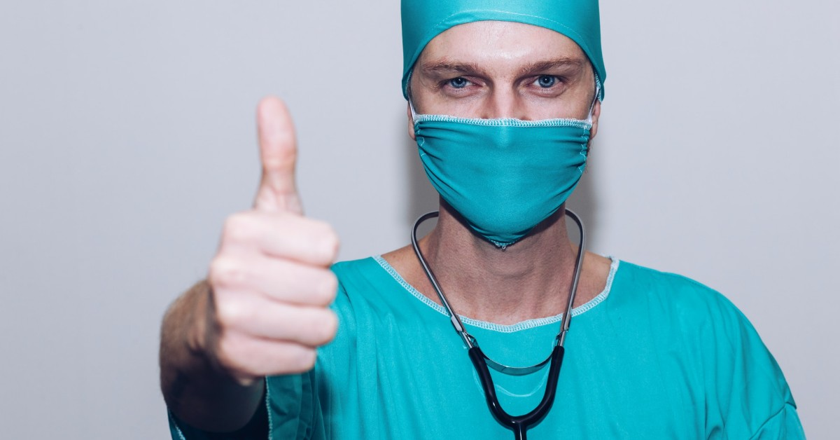 A doctor in a surgical cap and mask giving a thumbs up