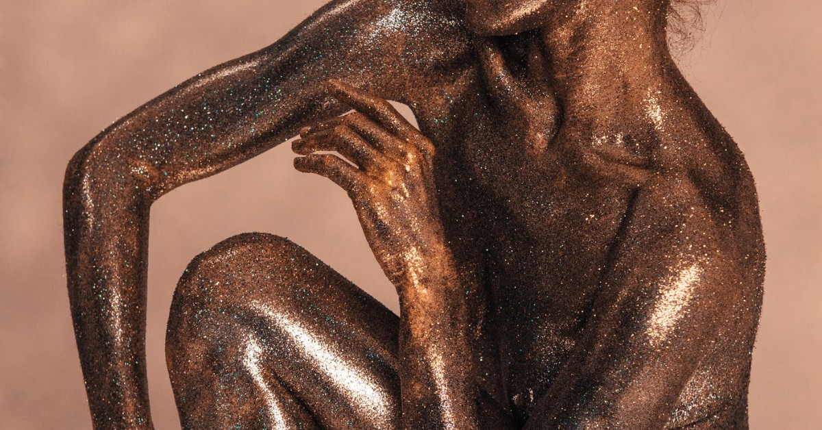 The upper body of a woman covered in copper sparkly paint