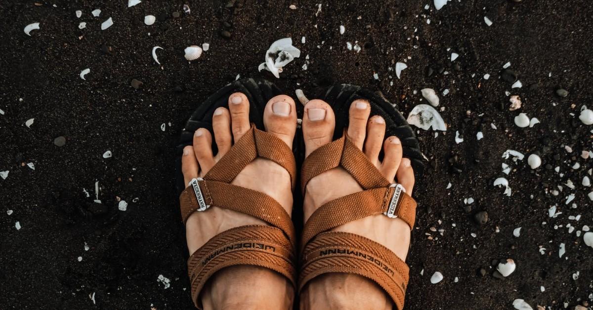 A pair of brown feet in brown sandals