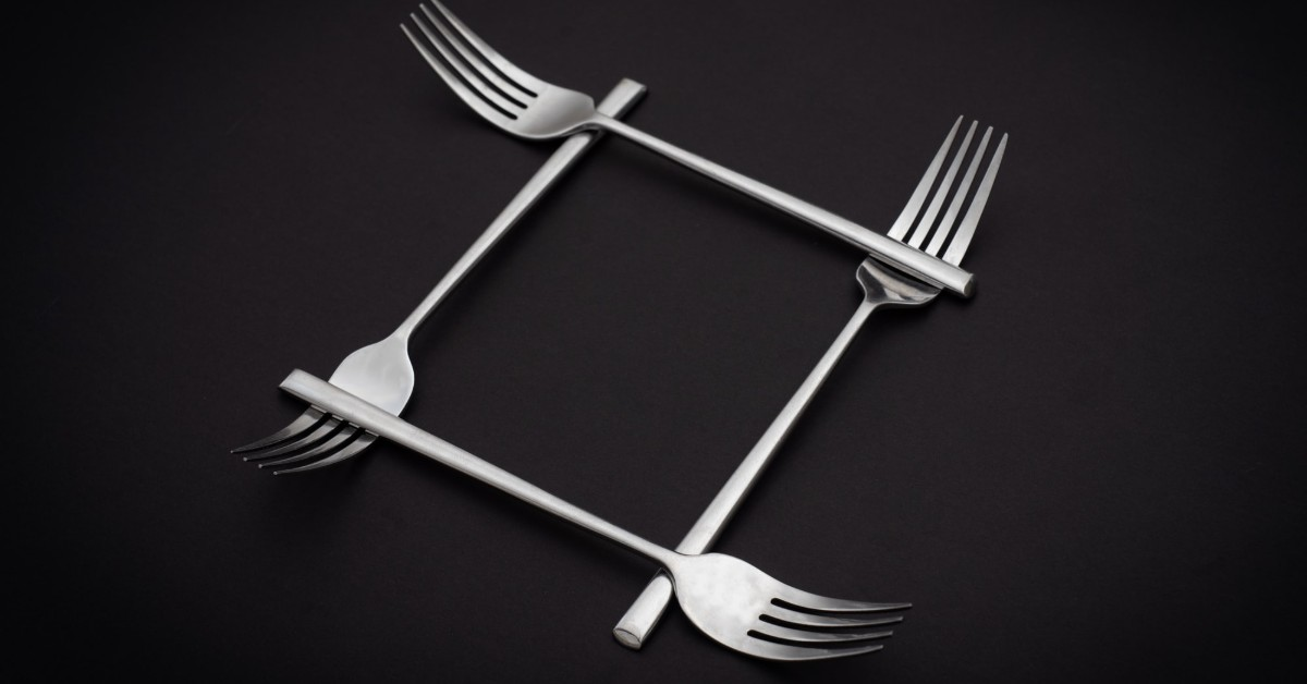 Four stainless steel spoons crisscrossing in a square pattern against a black background