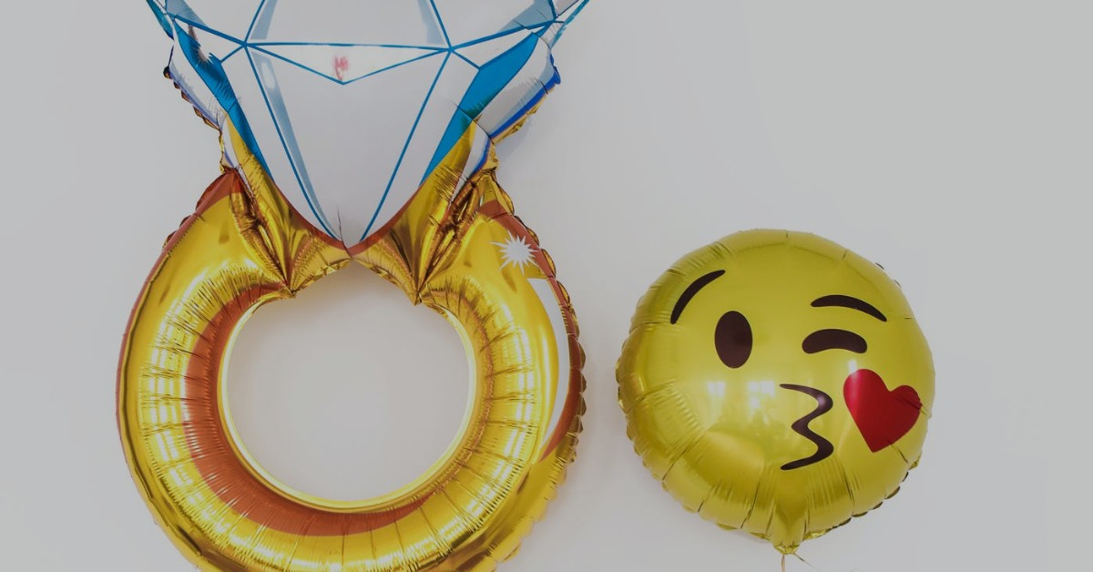Helium balloons shaped as a diamond ring and a kissing emoji