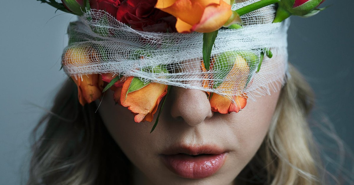 A woman with a white bandage and orange roses wrapped around and covering her eyes