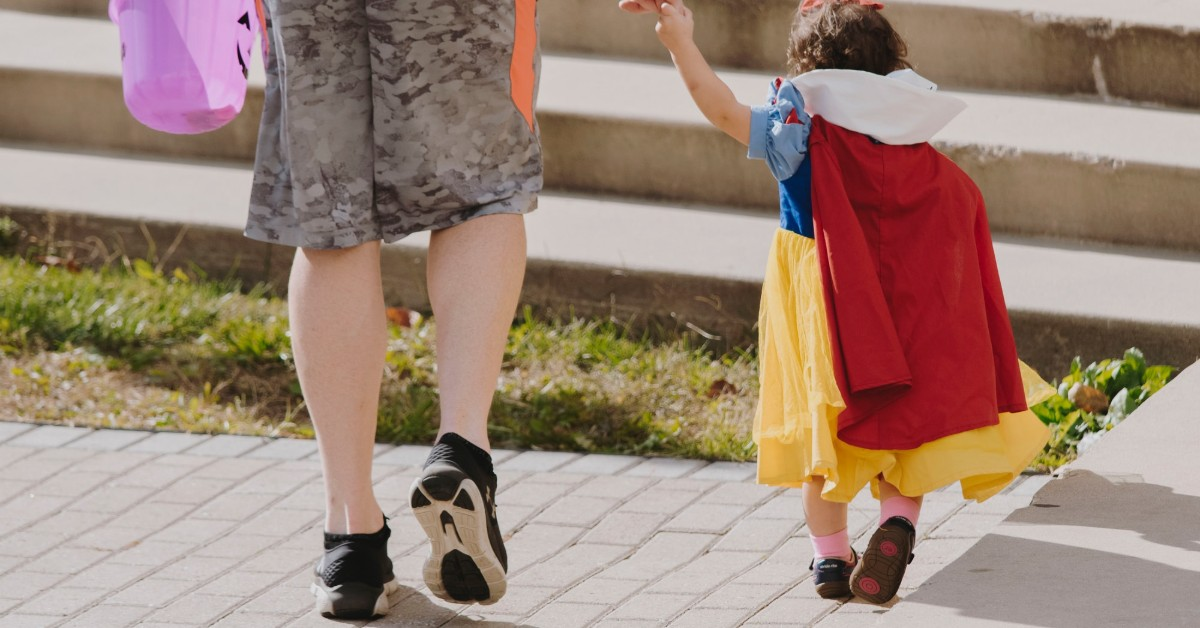 A toddler dressed in a Snow White costume holding her mother's hand and walking