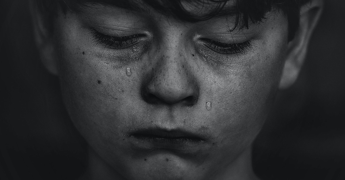 A black and white close up of a boy's crying face