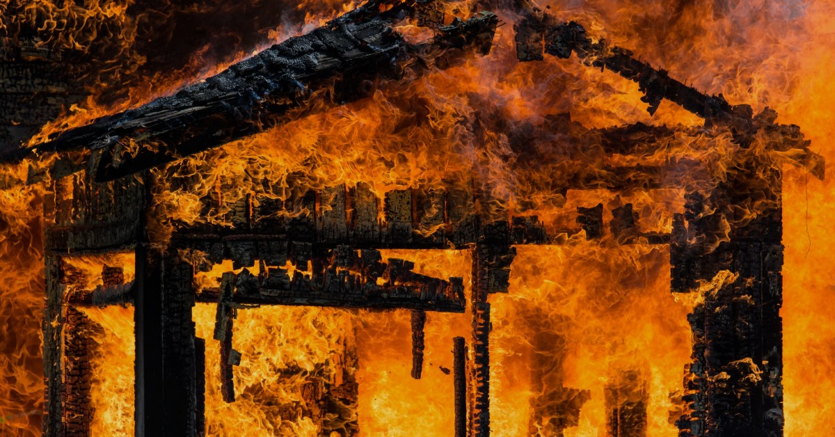 A burning house engulfed by flames of fire