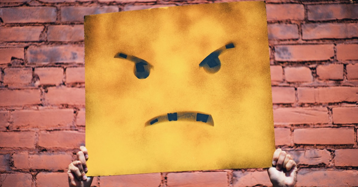 A pair of hands holding up a cardboard with an angry emoji face painted on it
