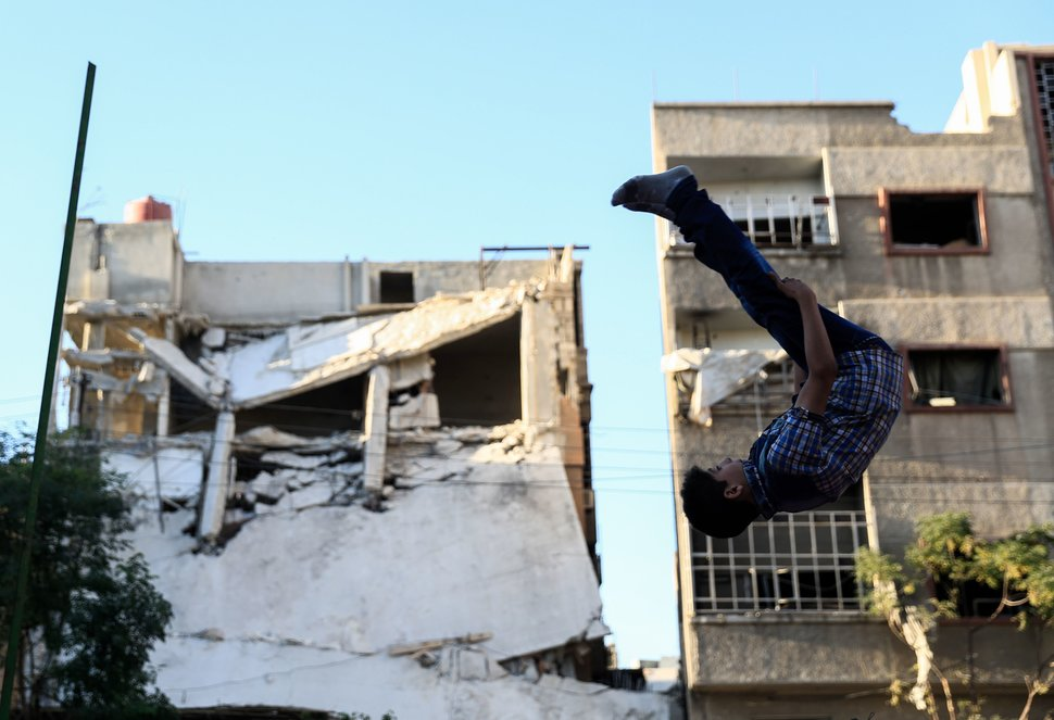 TOPSHOT - A Syrian boy jumps as he plays in the rebel-held town of Douma, on the eastern edges of the capital Damascus, on the second day of Eid al-Adha Muslim holiday on September 13, 2016. / AFP / Sameer Al-Doumy        (Photo credit should read SAMEER AL-DOUMY/AFP/Getty Images)