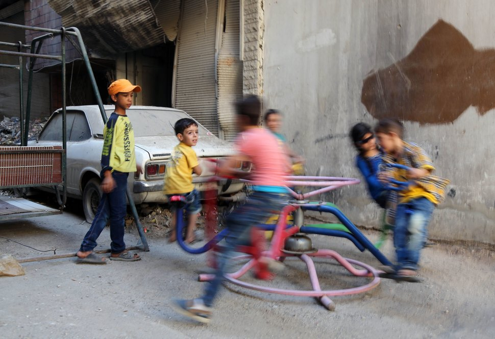 Syrian children play on a ride in the Syrian rebel-held town of Arbin, in the eastern Ghouta region on the outskirts of the capital Damascus, as they celebrate the Muslim Eid al-Adha holiday on September 13, 2016, the day after an internally backed ceasefire for Syria came into effect as part of a hard-fought deal to bring an end to the war between rebels and regime fighters.  / AFP / AMER ALMOHIBANY        (Photo credit should read AMER ALMOHIBANY/AFP/Getty Images)