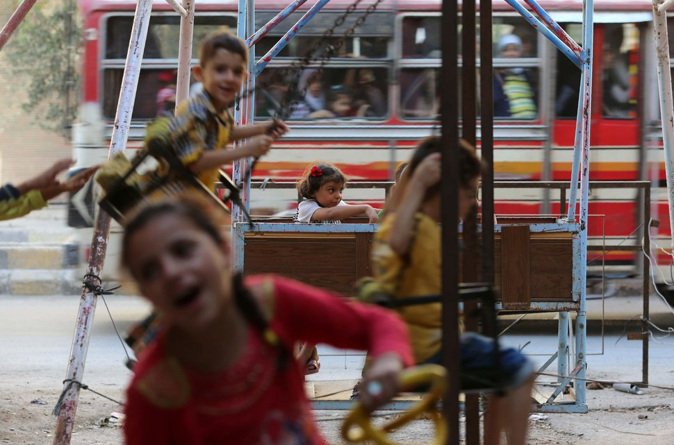 Syrian children play on swings in the Syrian rebel-held town of Arbin, in the eastern Ghouta region on the outskirts of the capital Damascus, as they celebrate the Muslim Eid al-Adha holiday on September 13, 2016, the day after an internally backed ceasefire for Syria came into effect as part of a hard-fought deal to bring an end to the war between rebels and regime fighters.  / AFP / AMER ALMOHIBANY        (Photo credit should read AMER ALMOHIBANY/AFP/Getty Images)