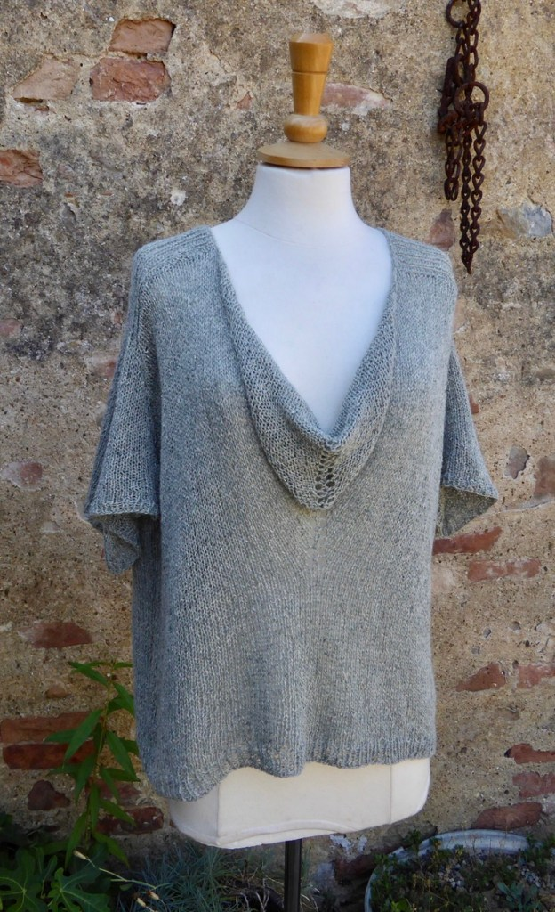 a full image of The Cowl Neckline Top from A Stitch in Time Vol. 1bphotpgraphed from the front against a brick and render wall.