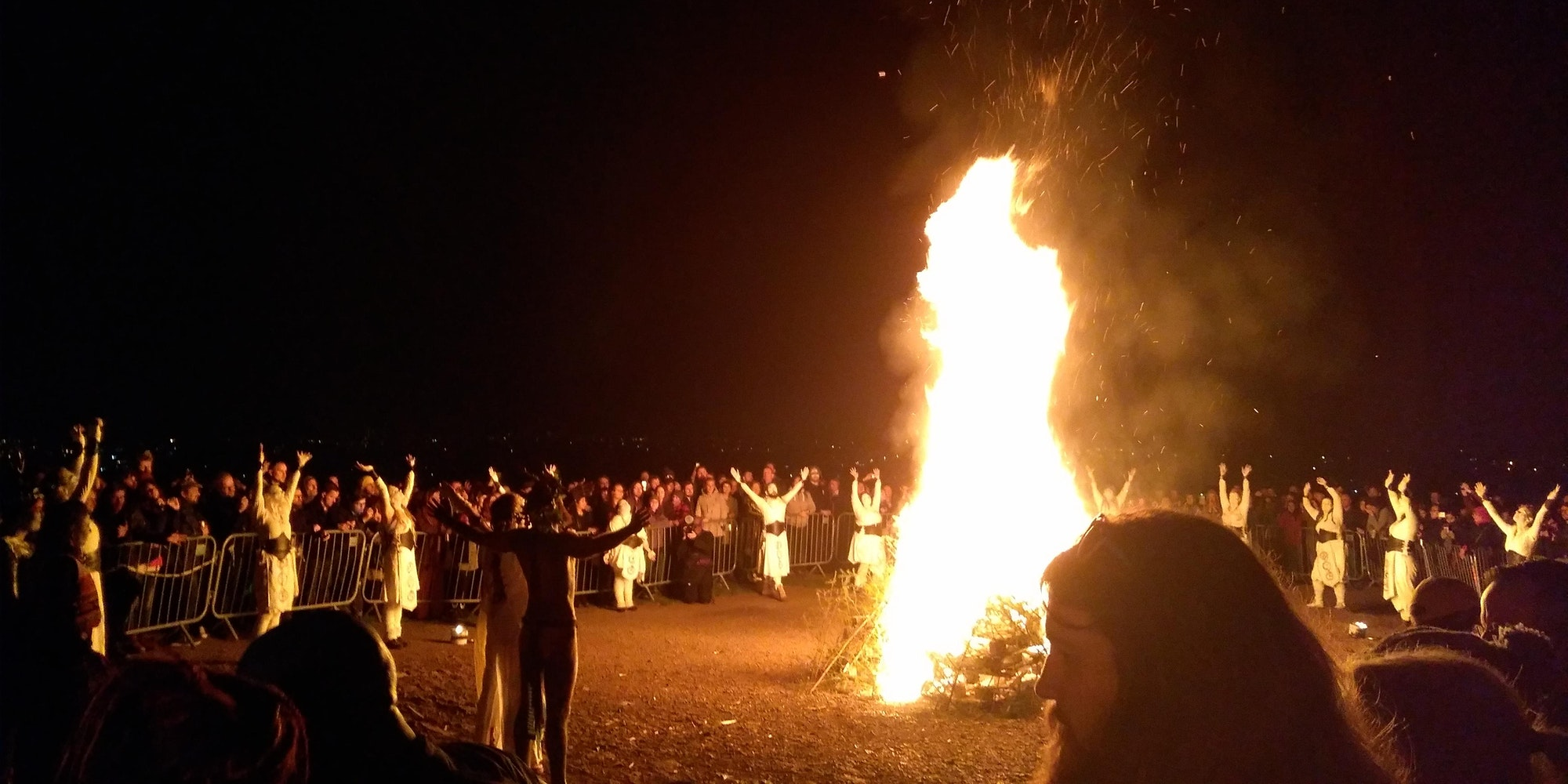 "Bonfire at the Beltane Fire Festival 2019, Calton Hill, Edinburgh. The reunited May Queen and Green Man face the fire, while dancers stop to raise their arms to heaven. Photo by ""Nyri0"" This file is licensed under the Creative Commons Attribution-Share Alike 4.0 International license."